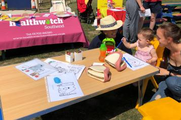 A Healthwatch employee at a childrens fun day engaging with families collecting local views and promoting good oral hygiene